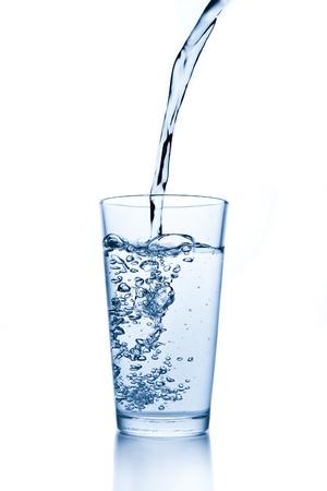 acqua che spruzza dal vetro isolato su sfondo bianco