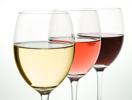 drie glazen met witte, rose en rode wijn