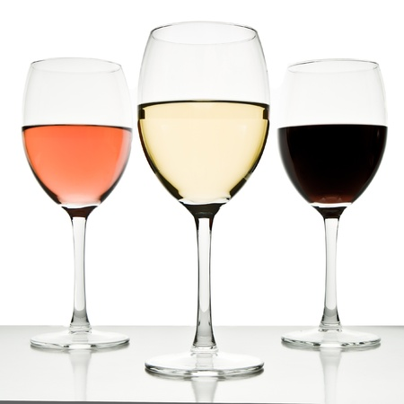 red and white wine: three glasses with white, rose and red wine