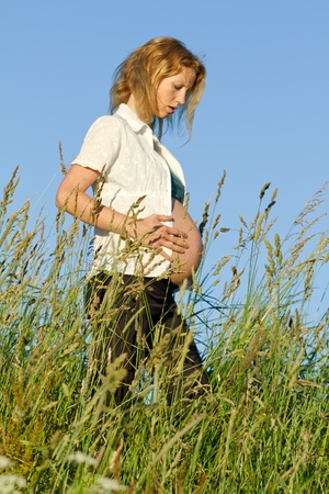 beautiful pregnant woman on a meadow with blue sky photo