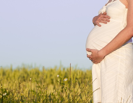 pregnant woman in white dress relaxing outdoors photo
