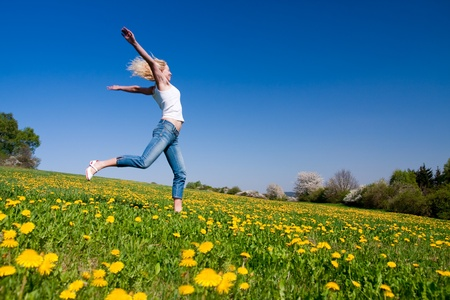 young female having fun on flowery meadow Stock Photo