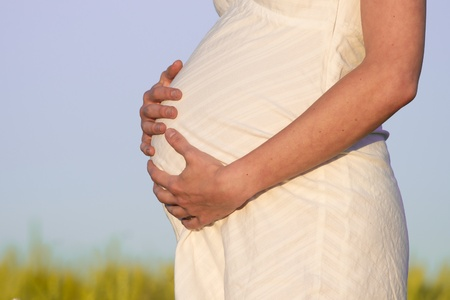 pregnant woman in white dress relaxing outdoors Stock Photo