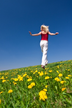 young woman having fun on a flowery meadow photo