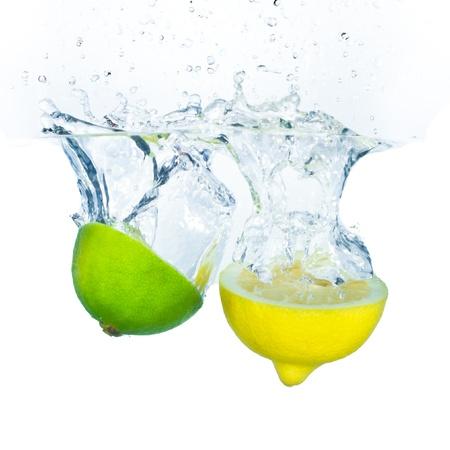 레몬: 흰색 배경에 고립 된 라임과 레몬 물이 튀는