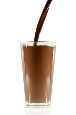 pouring chocolate milk into the glass isolated on white photo