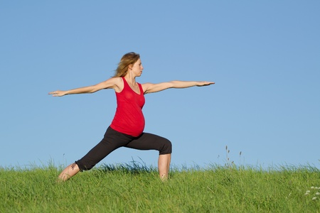 beautiful pregnant woman practicing yoga on a meadow photo