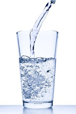 sediento: verter agua en un vaso sobre un fondo blanco