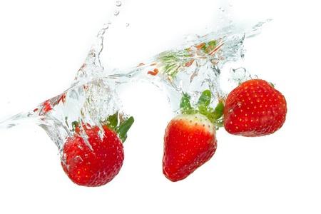 dropped: fresa fresca cay� en el agua con el chapoteo en los fondos blancos Foto de archivo
