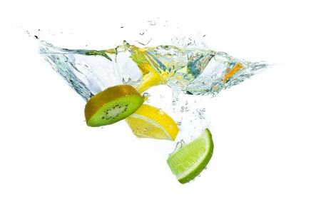 sliced citrus fruit with kiwi splashing isolated on white background photo