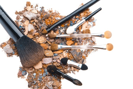 crushed eyeshadows with set of brushes isolated on white background photo