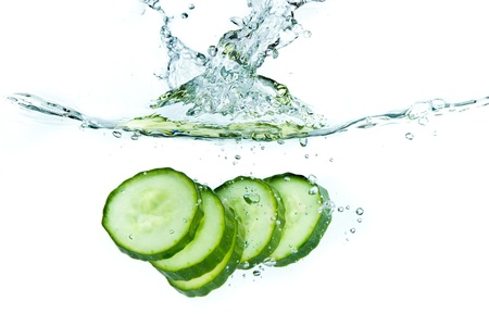 sliced cucumber splashing water isolated on white background photo