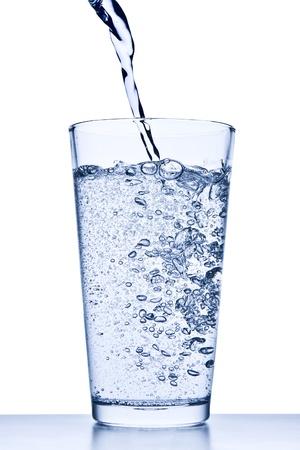 l'eau qui coule dans le verre sur fond blanc Banque d'images