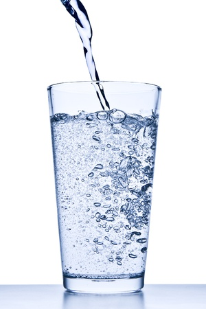 drinking soda: water pouring into glass on white background