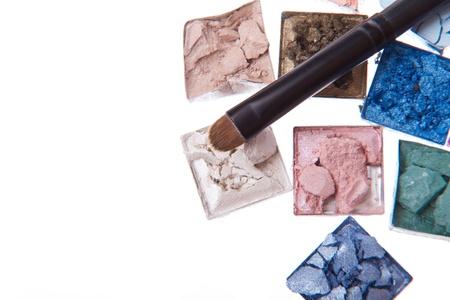 multicolored crushed eyeshadows with brush isolated on white background photo