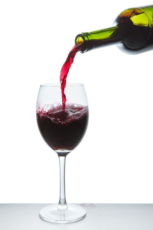 liquor bottle: red wine pouring into wine glass isolated Stock Photo
