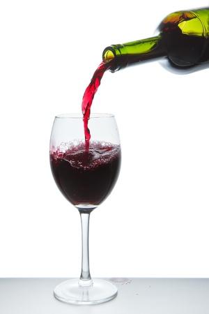 bottle liquor: verter el vino tinto en un vaso de vino aisladas Foto de archivo