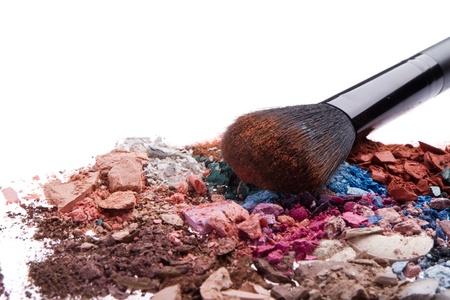 crushed eyeshadows with brush isolated on white background photo