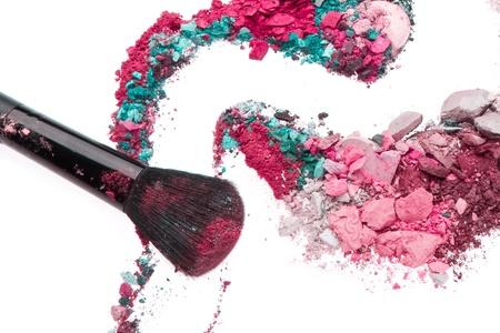 crushed eyeshadows mixed with brush isolated on white background photo