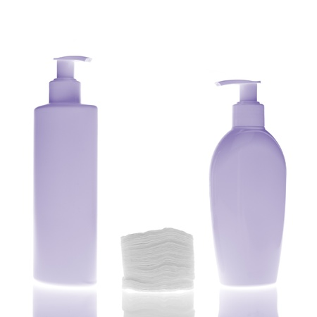 set of cosmetic bottles with cleaning pads isolated on white background photo