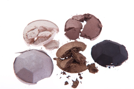 multicolored crushed eyeshadows with brush isolated on white background photo