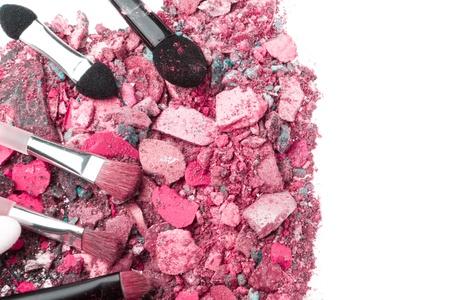crushed eyeshadows with set of brushes isolated on white background photo