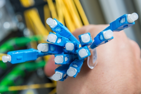 hand  of administrator holding bunch of optic fiber cables with connectors photo