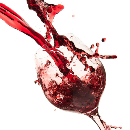 pouring red wine in goblet, isolated on white photo