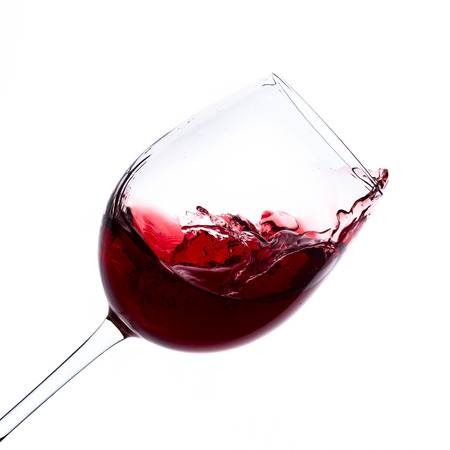 red wine splashing out of a glass, isolated on white Stok Fotoğraf