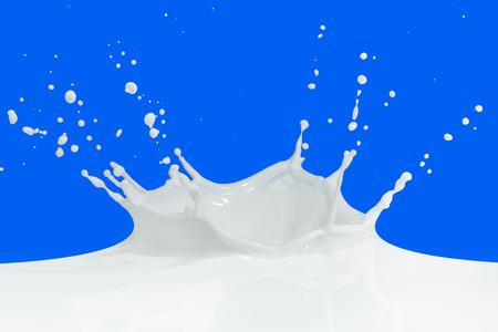 latte fresco: spruzzi di latte isolato su sfondo blu Archivio Fotografico