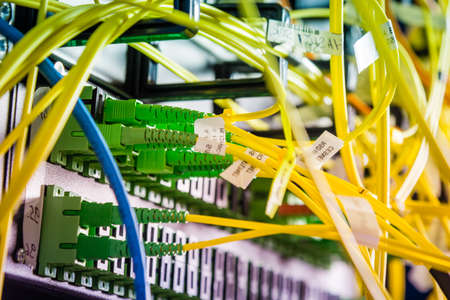 detail of server rack with fiber optic cables attached to front panel switch ports