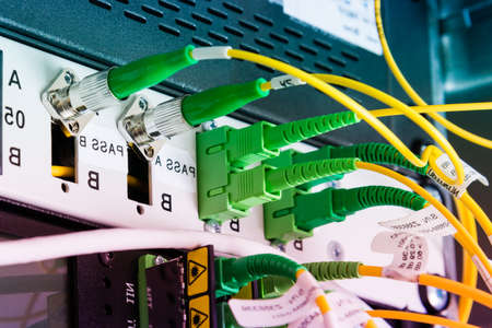 fiber optic cables plugged in network switch panel inside data center