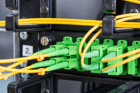 Fiber Optic cables connected to an optic ports - data switch in internet data center Stock Photo