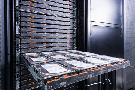 maintenance of hard drives inside data storage hosting center - open tray with cluster of hard disks waiting to be inspected