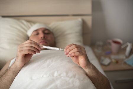 A young man lies in bed with heat. Patient with coronovirus infection 스톡 콘텐츠