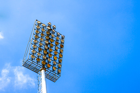 Lamp post over the sports stadium with blue sky background.