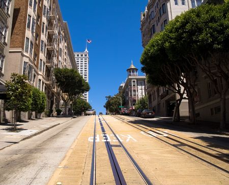 surrounding: Steep street in San Francisco with cable car rails and surrounding buildings.