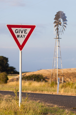 give the way: Give way road sign on a small rural road in New South Wales, Australia. A wind powered irrigation water pump is seen in background.