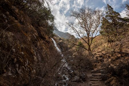 Hiking path to Gokyo near Dole with rocky hills and a small waterfall in Nepal Himalayas Stock Photo