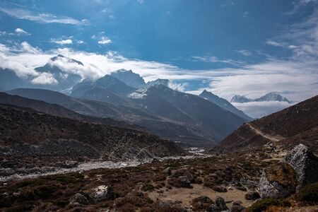 Landscape high in Nepal Himalayas with group of tourists on narrow path and moutain tops in the distance
