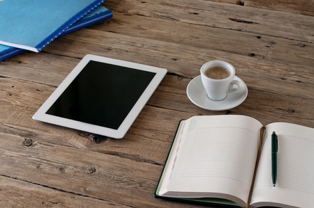 White tablet computer with a blank screen on the wooden table with a cup of black coffee and notepad.