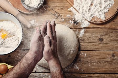 flour: Male baker prepares bread. Male baker slaps on dough.