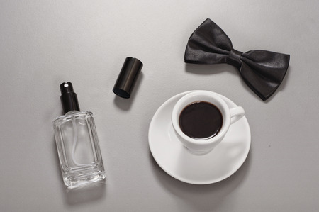 toilette: Cup of black coffee with a man bow tie and man eau de toilette. Stock Photo