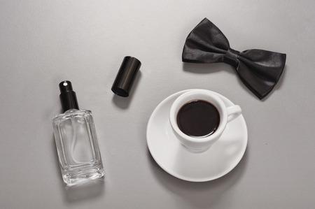 Cup of black coffee with a man bow tie and man eau de toilette. Foto de archivo