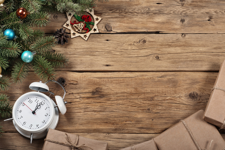 1 2 years: Branch of a Christmas tree with toys, Christmas presents and alarm clock on wooden background.