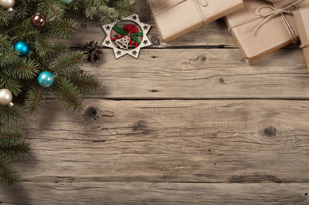 1 2 years: Branch of a Christmas tree with toys and Christmas gifts on wooden surface.