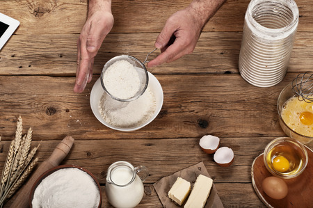 panadero: Hombre panadero tamiza la harina sobre una mesa de madera. Ingredientes para hornear. Vista superior Foto de archivo