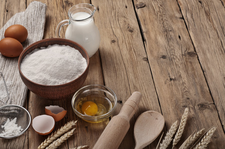 Flour, egg, milk on wooden table rustic kitchen. Ingredients for cooking flour products or dough close up. Stockfoto