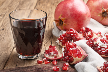 Pomegranate juice with pieces of Pomegranate on a wooden table closeup.