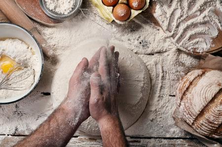 Male baker slaps on dough. Male baker prepares bread. Top view.